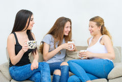 Three happy friends talking and drinking coffee or tea. Three happy friends talking and drinking coffee and tea sitting on a couch at home Royalty Free Stock Photography