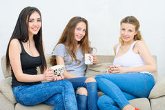 Three happy friends talking and drinking coffee or tea Royalty Free Stock Images