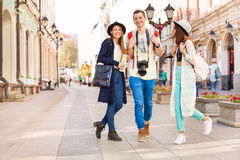 Three happy friends walking during sightseeing. On the European street during summer day time in Moscow Stock Photo