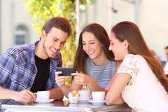 Three friends watching smart phone media content in a bar. Three happy friends watching smart phone media content sitting in a coffee shop royalty free stock photos