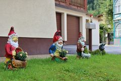 Happy garden gnomes in Böckstein. Three happy garden gnomes and a cat outside a house in Böckstein in Austria Royalty Free Stock Images