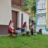 Happy garden gnomes in Böckstein. Three happy garden gnomes and a cat outside a house in Böckstein in Austria Stock Photo