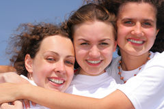 Three happy girl. Clothed in white t-shirt against a blue sky Stock Photography