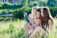 Three happy girl friends singing and playing guitar against blue sky outdoors Royalty Free Stock Photography