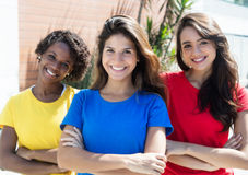 Three happy girlfriends in colorful shirts Royalty Free Stock Photo