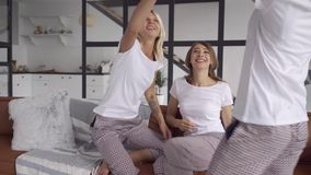 Three happy girlfriends in the same pajamas spending time together at home with alcohol. Hen-party, pajama party. Girls stock footage