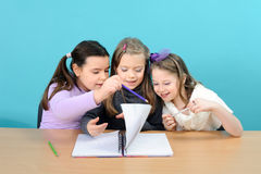Three happy girls doing their school work Royalty Free Stock Image