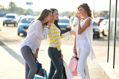 Three happy girls dressed in stylish casual clothes stand with shopping bags outside on a warm sunny day stock photo
