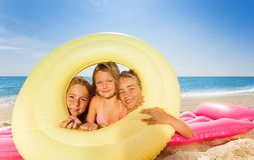 Cute girls looking through rubber ring at beach. Three happy girls friends on pink mattress looking through big rubber ring at the beach stock photos