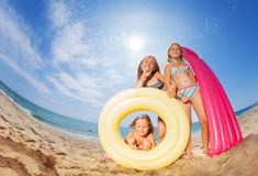 Three happy girls friends playing at sandy beach. Fish-eye picture of three preteen girls holding bright rubber ring and inflatable mattress, playing at sandy royalty free stock photo