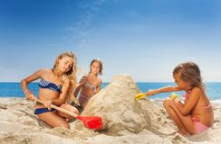 Three happy girls friends sculpting sandcastle Stock Image