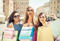 Three happy girls having fun. And making shopping Stock Photos