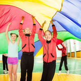 Three happy girls hiding under parachute`s canopy Stock Photos
