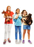Three happy girls holding their beloved pets. Three diverse girls standing holding their beloved pets cat, rabbit and dog Royalty Free Stock Photography