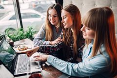 Three happy girls looks at laptop screen in cafe. Three happy girls looks at the laptop screen in cafe. Chocolate dessert and alcohol on the table Royalty Free Stock Photography