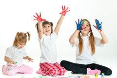 Three happy girls playing with finger colours Stock Photos