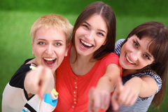 Three happy girls pointing fingers at you choosing Stock Photo