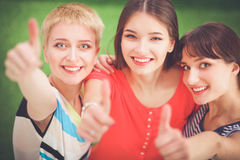 Three happy girls pointing fingers at you choosing.  Royalty Free Stock Image