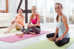 Three happy girls posing after group training. We are active. Three happy athletic girls posing after having group training while spending time in gym Stock Photos