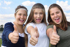 Three happy girls scream and thumb up outdoors Stock Photos