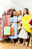 Three happy girls with shopping bags in the shop Royalty Free Stock Images