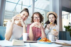 Unhealthy food. Three happy girls sitting in fast food cafe, looking at camera and eating unhealthy snack stock image