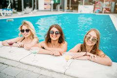 Three happy girls in sunglasses on the poolside. Three happy girls in swimsuits and sunglasses on the poolside. Resort holidays. Attractive women in the swimmimg Royalty Free Stock Images