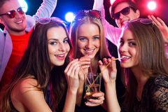 Three happy girls. Together drinking cocktails at a party Stock Photo