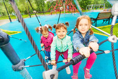 Three happy girls try climbing the grid. Of playground in summer time Stock Photo