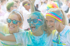 Three happy girls wearing sun glasses taking a selfie. STOCKHOLM - MAY 23, 2015: Three happy girls covered with color powder wearing sun glasses taking a Stock Image