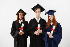 Three happy graduates smiling holding diplomas looking at camera over white background. Royalty Free Stock Image