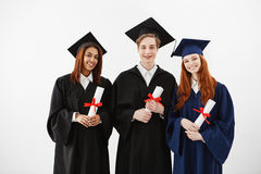 Three happy graduates smiling holding diplomas looking at camera over white background. Three happy graduates in mantles smiling holding diplomas looking at Royalty Free Stock Photos