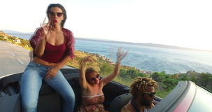 Three happy hipster friends having fun in convertible stock video footage