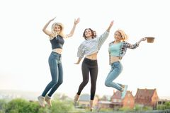 Three happy joyful young women jumping and laughing together at park Royalty Free Stock Images