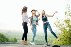 Three happy joyful young women jumping and laughing together at park Stock Images