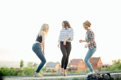 Three happy joyful young women jumping and laughing together at park Stock Image