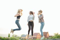 Three happy joyful young women jumping and laughing together at park Royalty Free Stock Photography