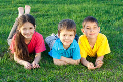 Three happy kids lying on the field Stock Photos