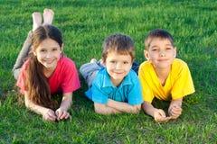 Three happy kids lying on the field Stock Photos