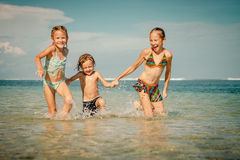 Three happy kids playing on beach Stock Photo