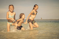 Three happy kids playing on beach Royalty Free Stock Image