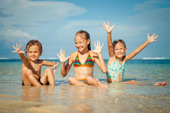 Three happy kids playing on beach Stock Photos