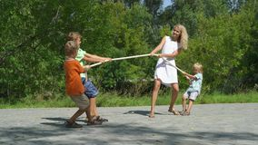 Three happy kids playing tug-of-war in city park with mum. Children and recreation,  Summer fun stock video footage