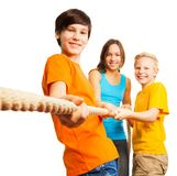 Three happy kids pull the rope. Team concept three happy kids pull the rope royalty free stock photo