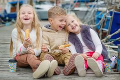 Three happy little children sit on the pier. And snack Stock Image