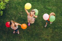 Three happy little kids playing with colorful balloons royalty free stock image