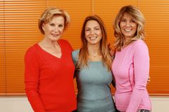 Three happy mature woman with different age together in front of an orange background stock images