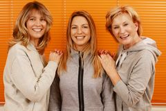 Three happy mature woman with different age together in front of an orange background stock photography