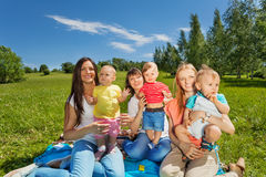 Three happy mothers holding cute babies in park Stock Photos