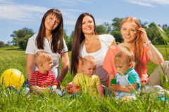 Three happy mothers with their babies sitting Stock Photo